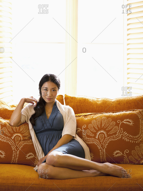 Beautiful woman relaxing on sofa at a luxury resort in Napa Valley, California