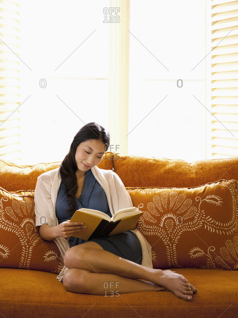 Beautiful woman reading a book relaxing on sofa at a luxury resort in Napa Valley, California