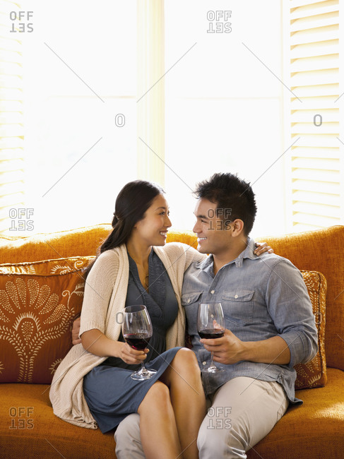 Chinese couple sitting on sofa of luxury resort hotel room drinking wine in Napa Valley, California