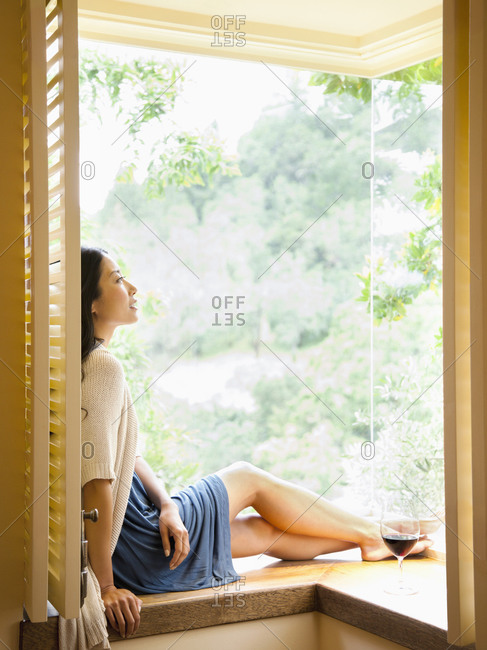 Beautiful woman sitting in window of luxury resort hotel room looking out at nature