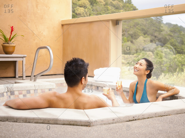 Chinese couple relaxing in hot tub at luxury spa drinking champagne overlooking wine country