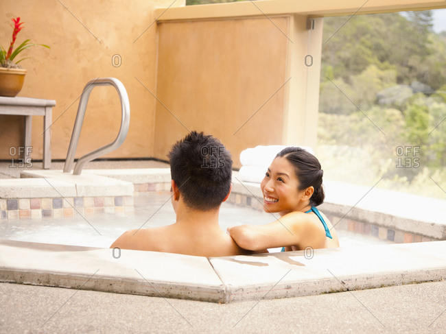 Chinese couple relaxing in hot tub at luxury spa overlooking wine country in California