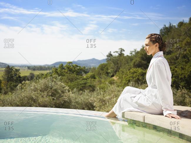 Woman in bathrobe sitting on edge of infinity pool at a luxury resort overlooking Napa Valley, California