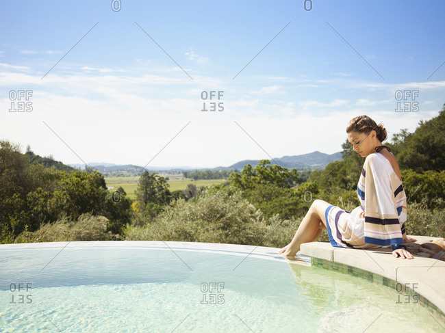 Woman in dress sitting on edge of infinity pool at a luxury resort overlooking Napa Valley, California