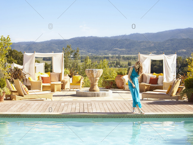 Beautiful woman dipping her toe in the pool at a luxury resort overlooking wine country in Napa Valley California