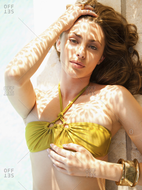 Close up portrait of a beautiful woman fashion model lying on the edge of a pool at a luxury resort in California