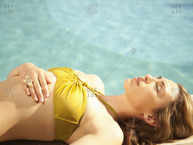 Close up portrait of a beautiful woman fashion model in a bikini lying on the edge of a pool at a luxury resort in California