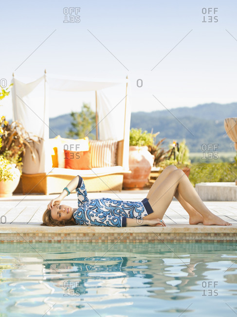 Beautiful woman lying on the edge of a pool in a California luxury resort overlooking wine country