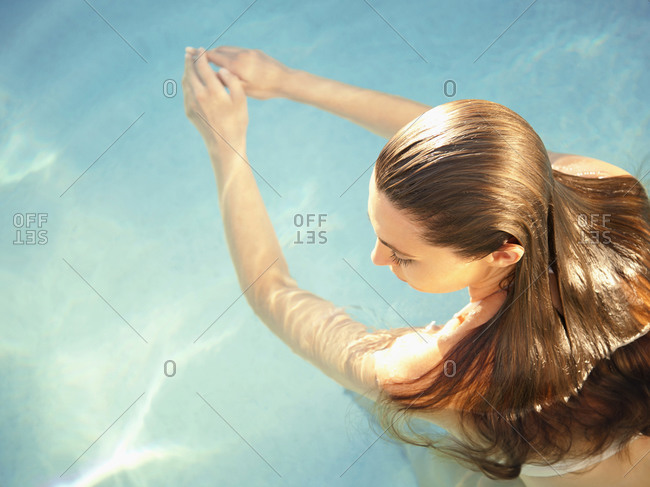 Rear overhead view of woman in water with arms outstretched in front of her