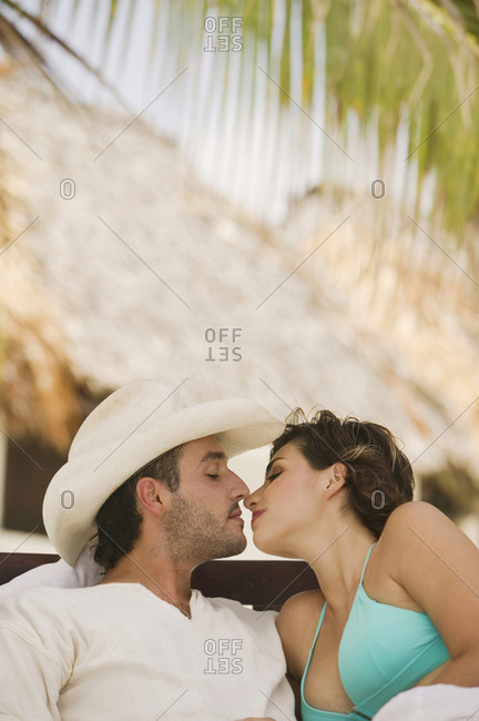 Couple kissing outdoors under the shade