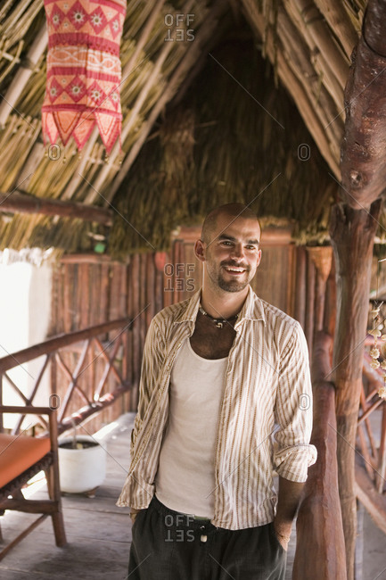 Young man smiling in a straw hut