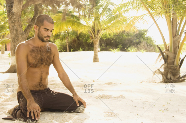 Young man kneeling in the sand meditating
