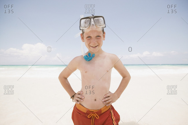 Young boy with snorkel smiling at the beach