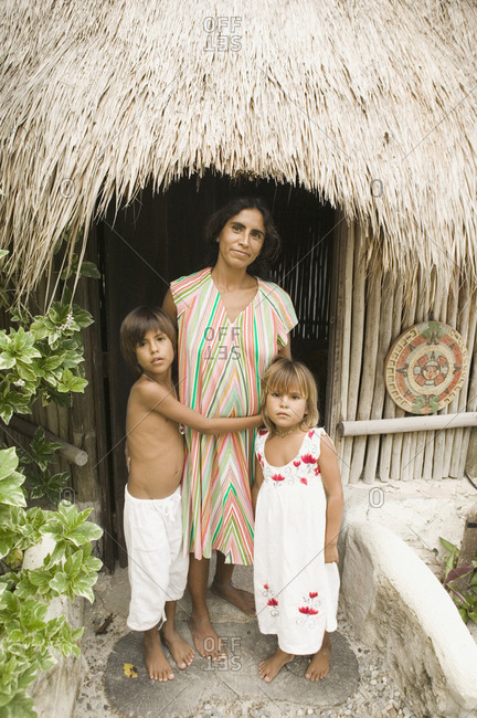 Mother posing with her children outside a straw hut
