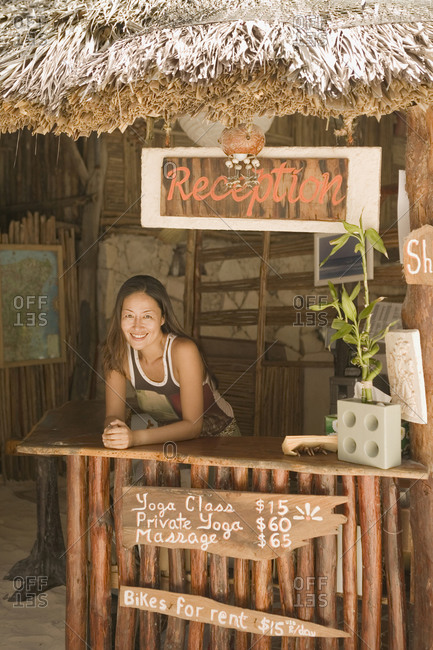 Young woman working at a beach reception desk
