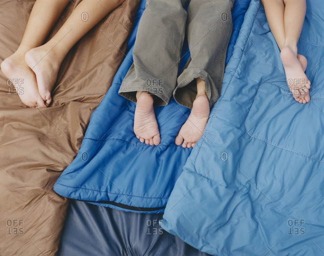 Three people, an adult and two boys lying on sleeping bags, knees down, bare feet.