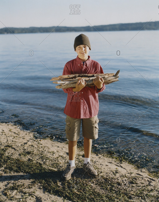 Portrait of adolescent boy holding pile of firewood on beach