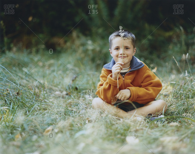 A young boy sits in field of tall grass, holding blade of grass