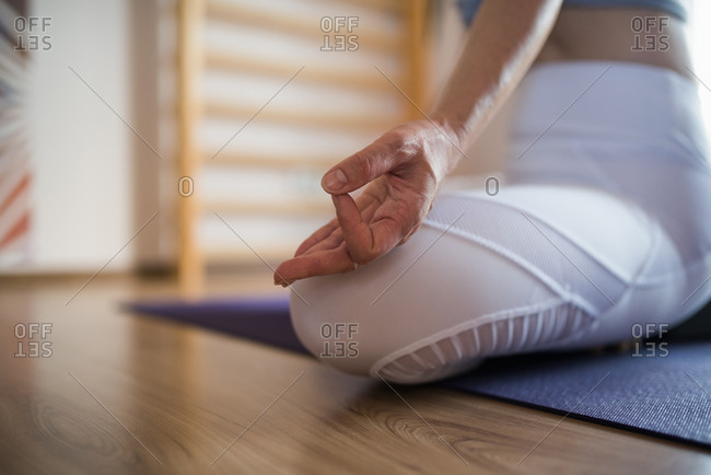 Woman in the studio sitting and meditating in a yoga position