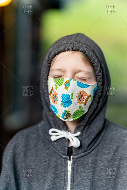 Young person wearing face mask with eyes closed during COVID pandemic