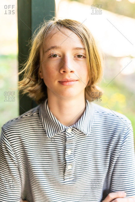 Candid portrait of teenage boy smiling with shoulder length hair