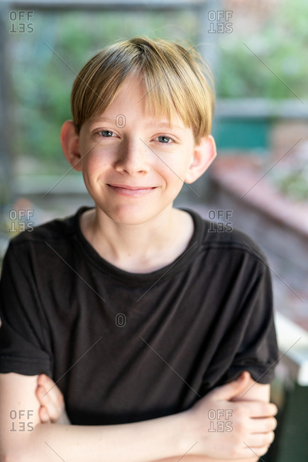 Candid portrait of tween boy smiling and looking at camera outside