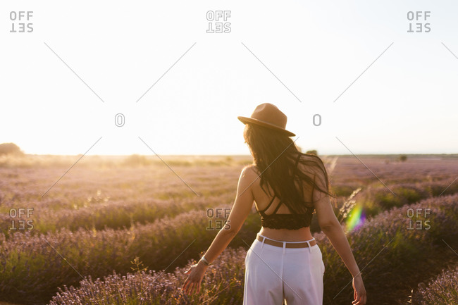 Young brunette woman on her back with a hat in a lavender field