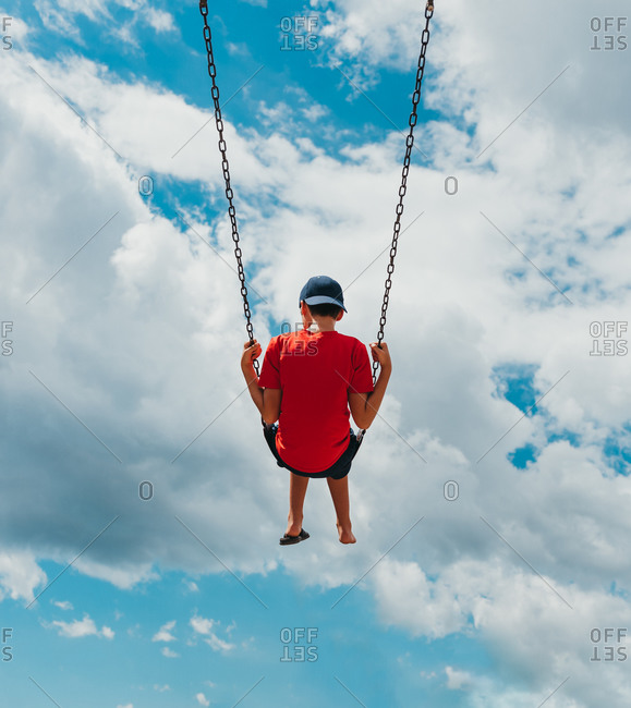 Rear view of boy on a swing with only cloudy sky in the background.