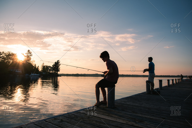 Father and son fishing on a dock of lake at sunset in Ontario, Canada.