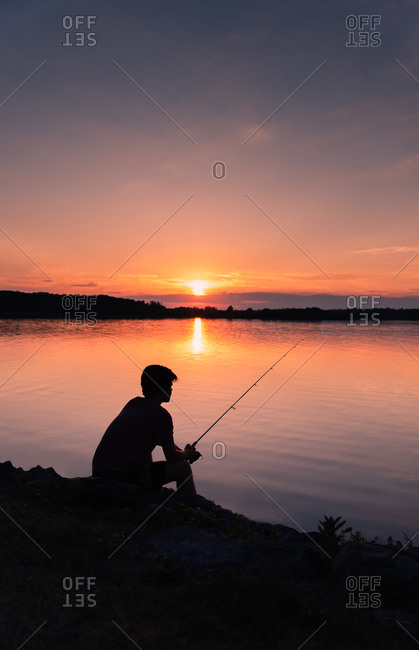 Adolescent boy fishing on shore of lake at sunset in Ontario, Canada.