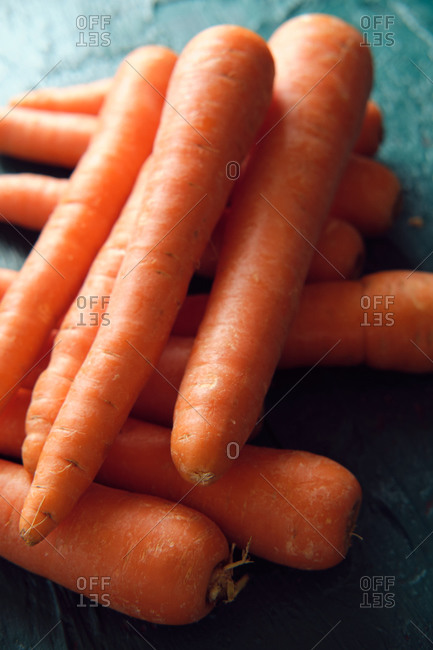 Several orange carrots on a green background