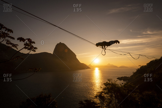 Beautiful sunrise view of man walking on highline with Sugar Loaf