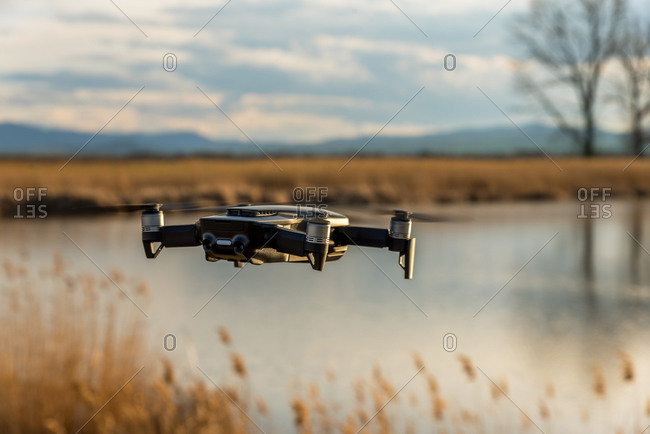 Small modern drone hovering taking picture of sunset.