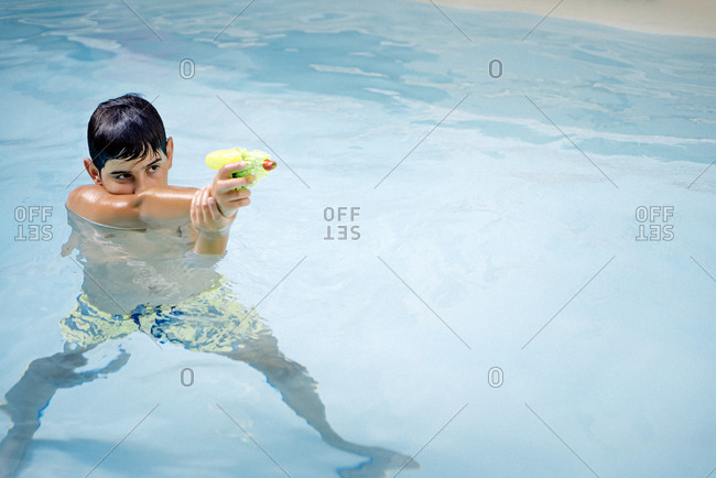 Handsome, dark-haired boy playing with a water gun in the pool water