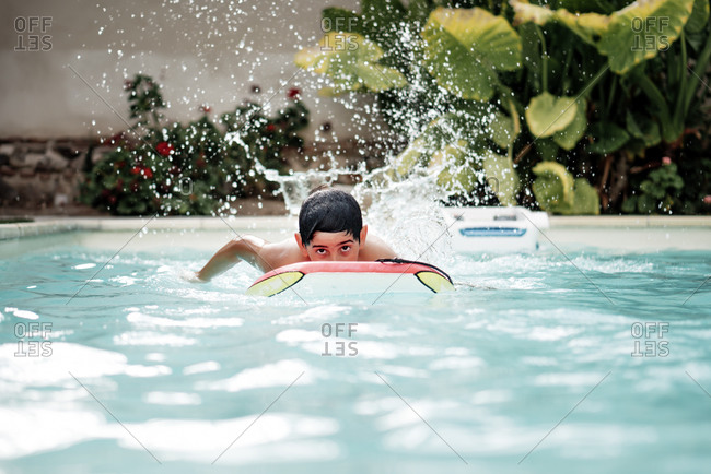 Handsome and dark-haired boy playing with a body surf board in the pool
