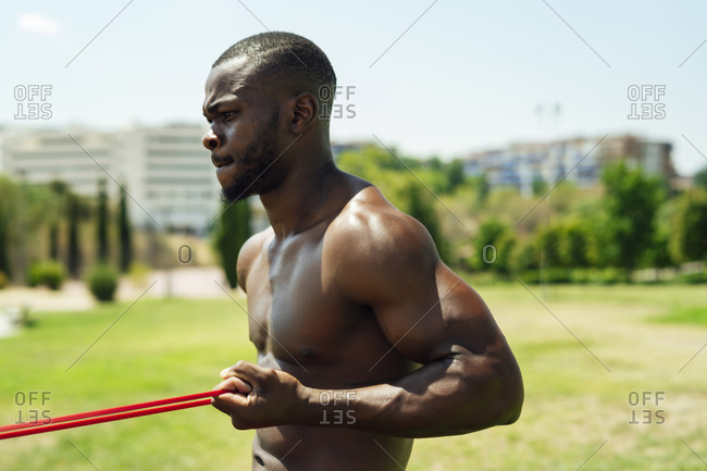 Young athlete doing biceps exercise with rubber bands