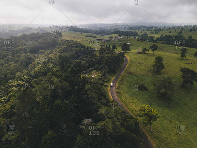 Aerial shot driving through Millaa Millaa town surroundings in monsoon season at Tropical Queensland, Australia