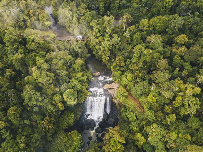 Aerial shot of Zillie Falls surrounded by lush green forest while a van driving through a bridge crossing in Tropical Queensland, Australia