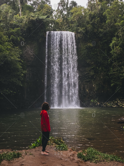Rearview of a young woman looking at the waterfall while standing, Millaa Millaa Falls, Tropical Queensland, Australia.