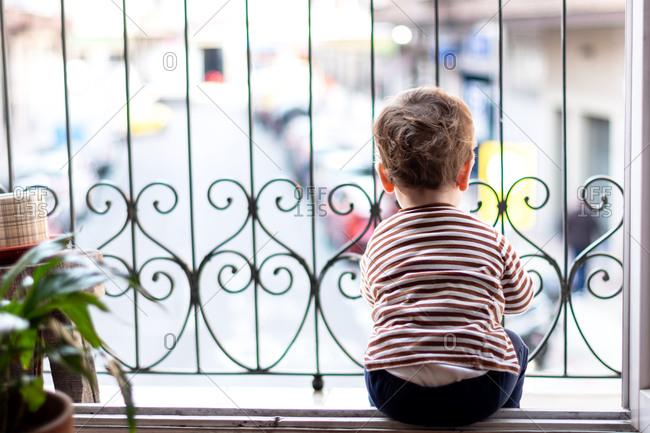 Bored kid staring off the balcony in quarantine.