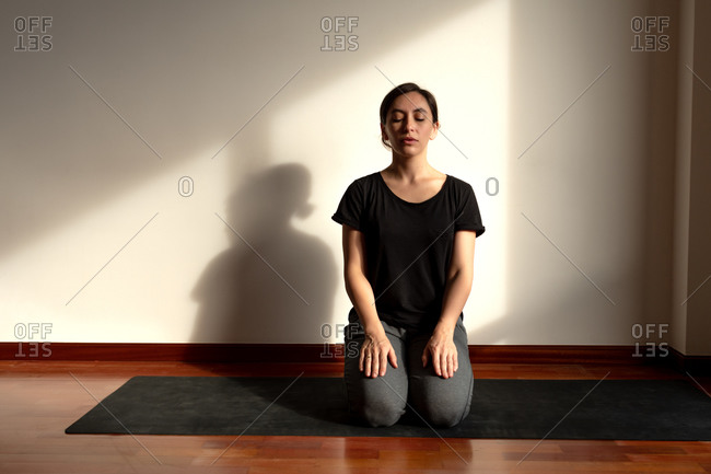 Woman learning to do yoga at home from a distance.