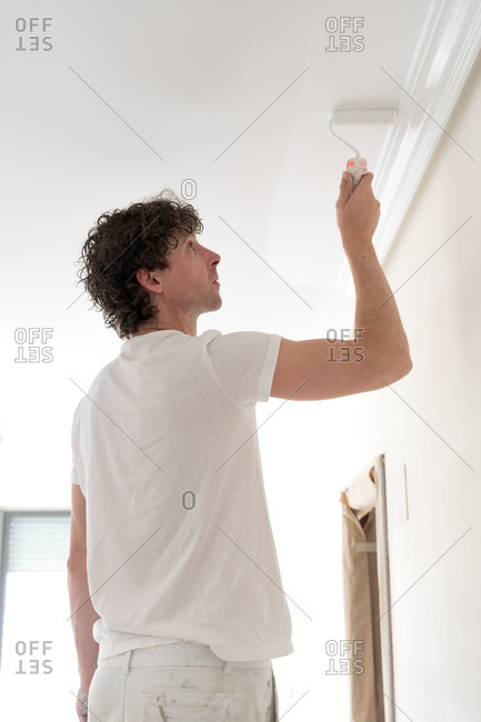 Worker painter painting the ceiling of the interior of a house in white.
