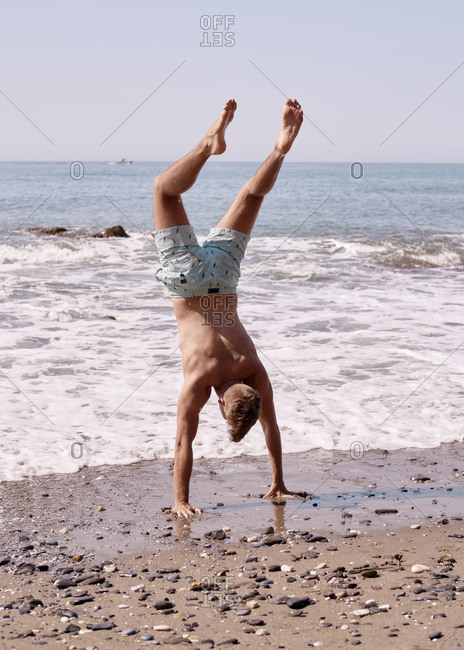 Young man does stunts with his hands on the beach