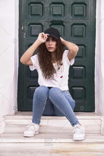 Young woman puts her cap in front of a wooden door