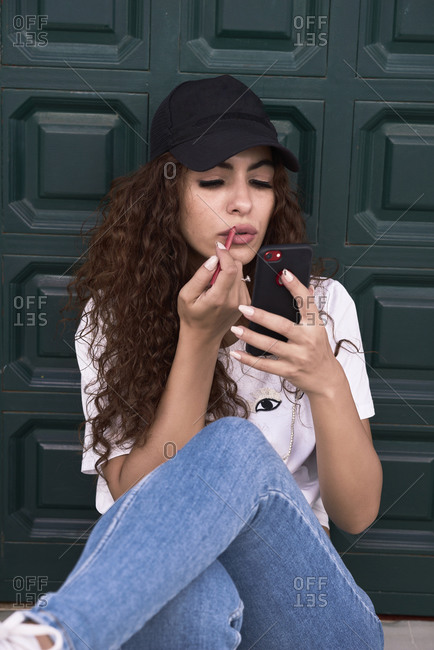 Young woman puts on lipstick sitting in front of a wooden door