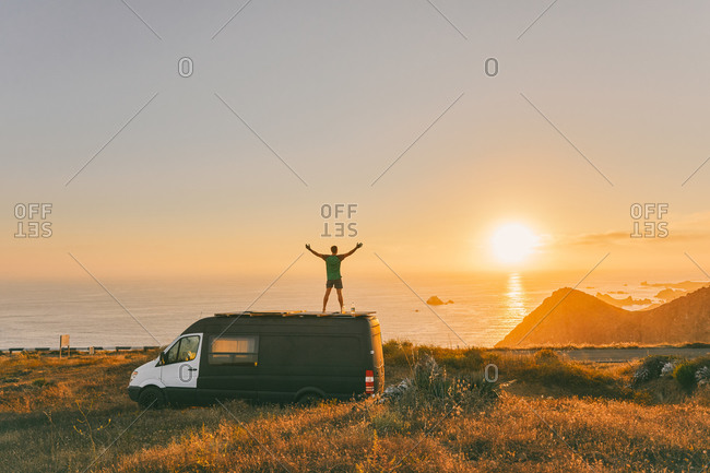 Young man on sprinter van with arms wide open in front of sunset on cliff in Baja, Mexico.