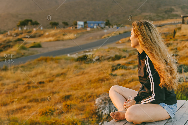 Young woman on sprinter van roof looking at sunset in Baja, Mexico.