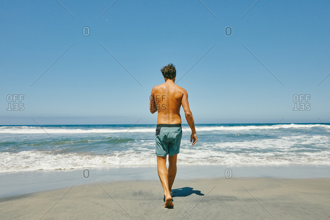 Young man walking shirtless to pacific ocean on beach in Baja, Mexico.