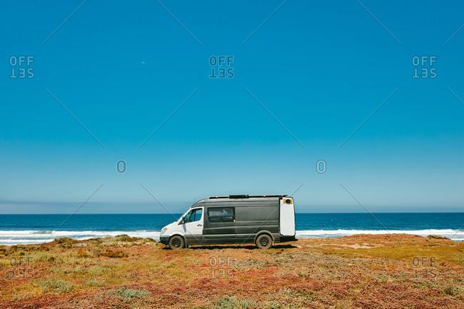 Camper van parked on ocean cliff beach during summer in Baja, Mexico.