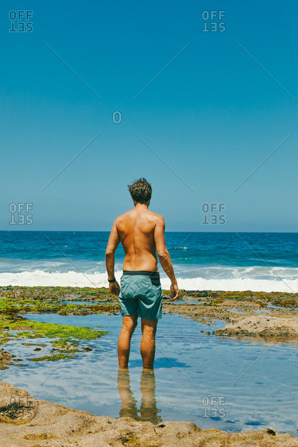 Young man standing in water looking out to ocean from bluffs in Baja.